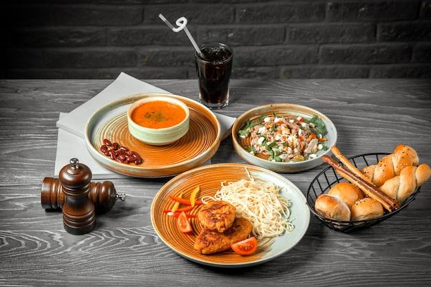 Vista frontal primeiro segundo e prato principal sopa de lentilha salada e costeletas com macarrão e um refrigerante em cima da mesa