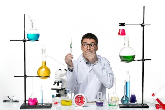 Vista frontal, químico masculino em terno médico branco segurando injeção em laboratório de covidemia de ciência de vírus de fundo branco