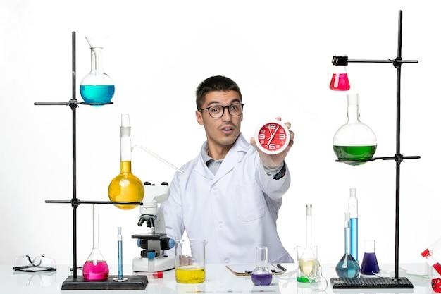 Vista frontal, químico masculino em terno médico branco segurando relógios no fundo branco vírus doença ciência laboratório covid