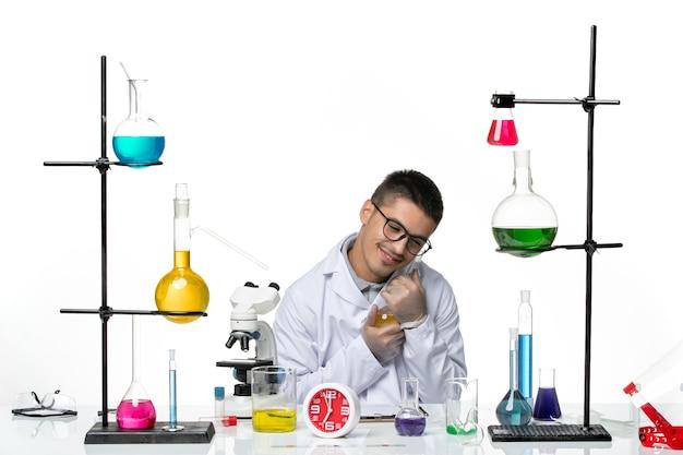 Vista frontal, químico masculino em terno médico branco segurando solução em pandemia de vírus ciência covid laboratório
