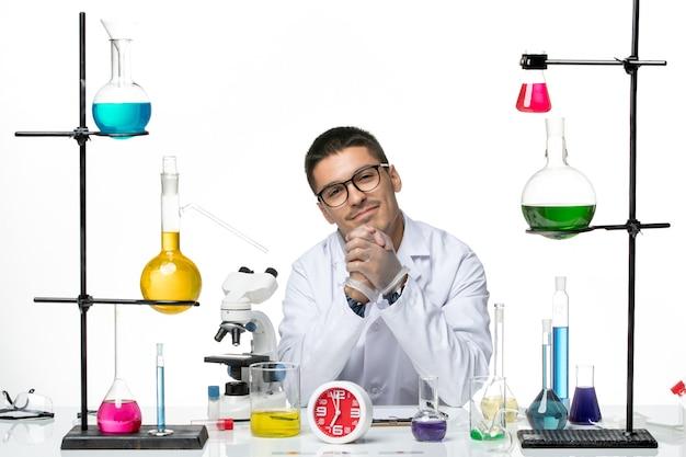 Vista frontal, químico masculino em terno médico branco sentado e sorrindo no laboratório de covidemia de ciência de vírus de fundo branco