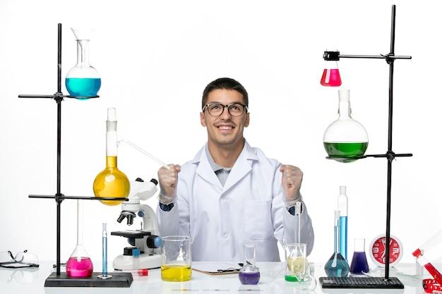 Vista frontal, químico masculino, terno médico, sentado com soluções sobre fundo branco, vírus covid doença ciência