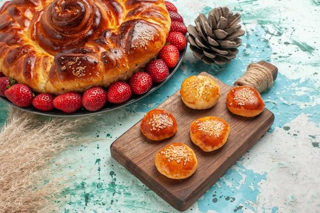 Vista frontal redonda deliciosa torta com morangos vermelhos frescos e bolos na superfície azul claro torta de açúcar biscoito biscoito doce