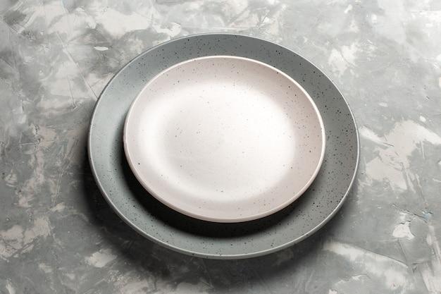 Vista frontal redondo prato vazio cinza colorido com placa branca na mesa cinza.