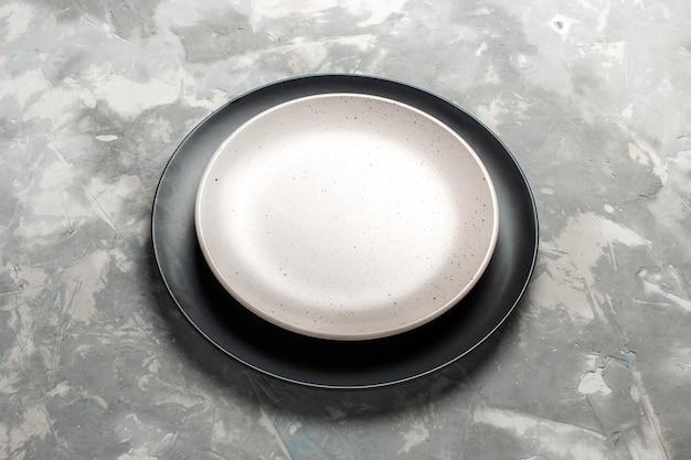 Vista frontal redondo prato vazio preto colorido com placa branca na mesa cinza.