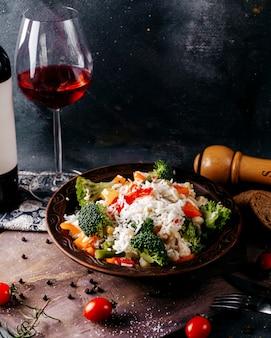Vista frontal refeição de legumes vitamina colorida enriquecida com garrafa de vinho tinto na mesa cinza