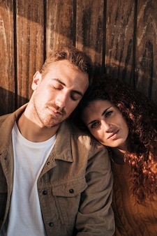 Vista frontal relaxante casal com fundo de madeira