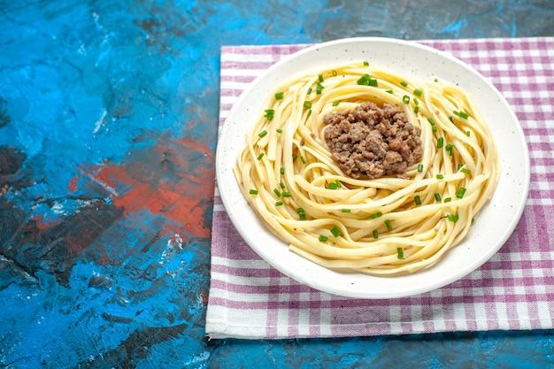 Vista frontal saborosa massa italiana com carne moída em prato de massa de cor azul.