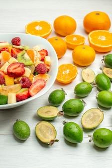 Vista frontal saborosa salada de frutas com feijoas frescas e tangerinas em uma árvore de frutas suaves de frutas brancas
