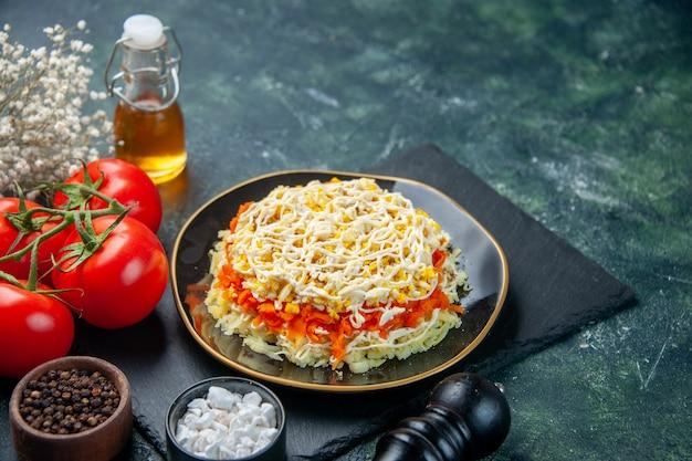 Vista frontal saborosa salada de mimosa dentro do prato com tomates em fundo azul escuro