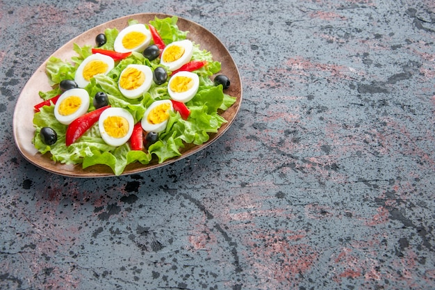 Vista frontal saborosa salada de ovo com salada verde e azeitonas em fundo claro