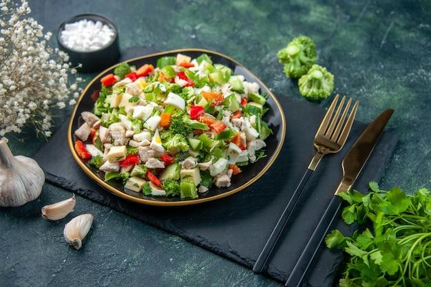 Vista frontal saborosa salada de vegetais dentro do prato com garfo em fundo escuro