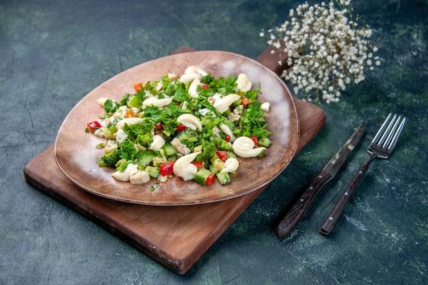 Vista frontal saborosa salada de vegetais dentro do prato com talheres em fundo azul escuro