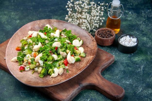 Vista frontal saborosa salada de vegetais dentro do prato em fundo azul escuro
