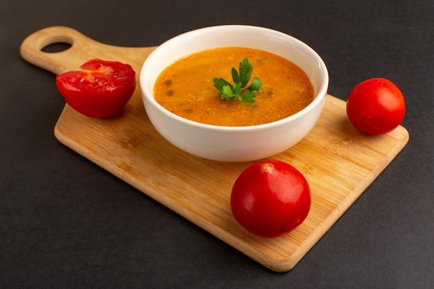 Vista frontal saborosa sopa de vegetais dentro do prato, juntamente com os tomates na mesa escura.