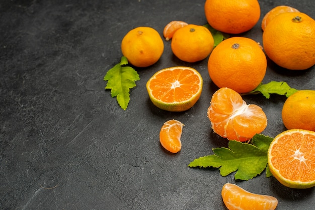 Vista frontal saborosas tangerinas suculentas em fundo escuro cor laranja frutas exóticas foto cítrica azeda