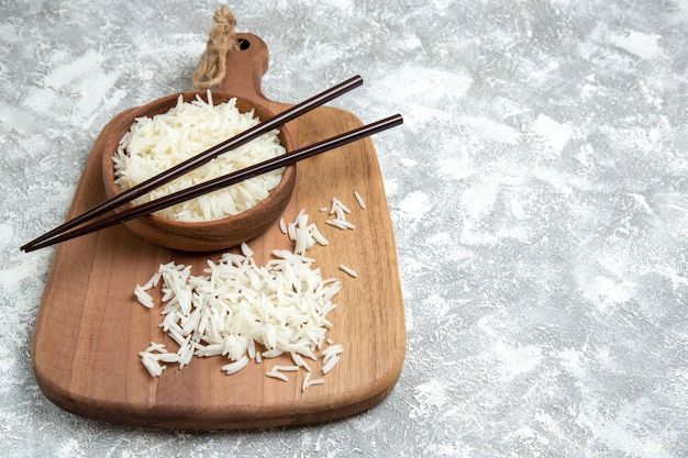 Vista frontal saboroso arroz cozido dentro de um prato marrom com palitos no espaço em branco