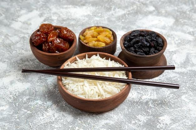 Vista frontal saboroso arroz cozido dentro de um prato marrom com passas em uma mesa branca clara