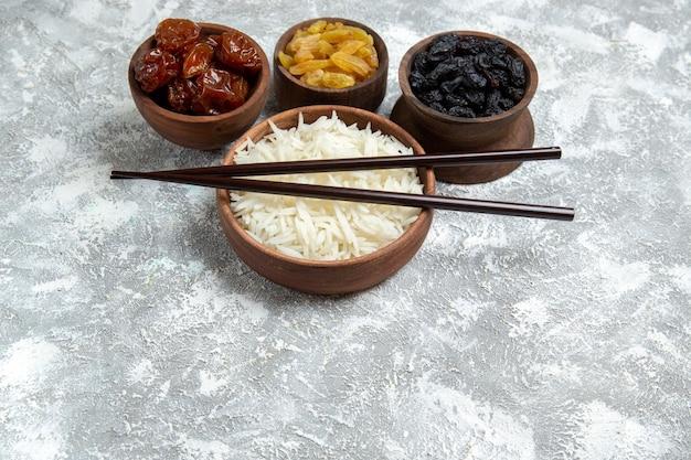 Vista frontal saboroso arroz cozido dentro de um prato marrom com passas na mesa branca