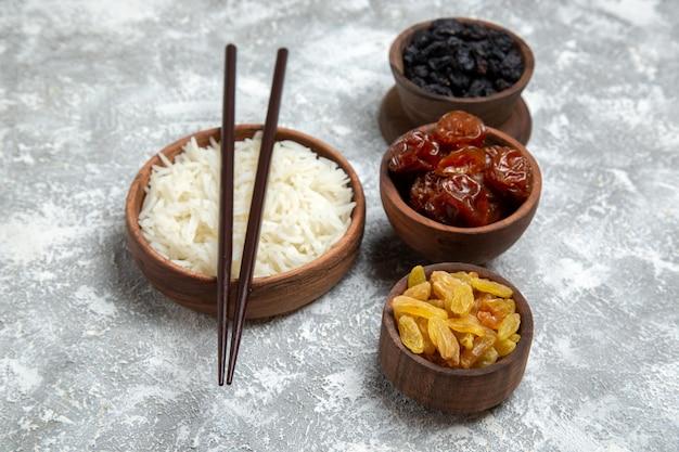 Vista frontal saboroso arroz cozido dentro de um prato marrom com passas no espaço em branco
