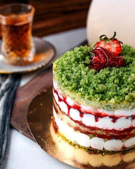 Vista frontal saboroso bolo colorido bolo de frutas, juntamente com chá quente no chão claro