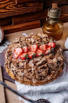 Vista frontal saboroso bolo com chocolate e morangos fatiados vermelhos frescos no chão marrom