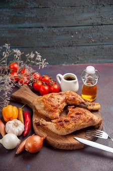 Vista frontal saboroso frango frito com legumes frescos e temperos em um espaço escuro