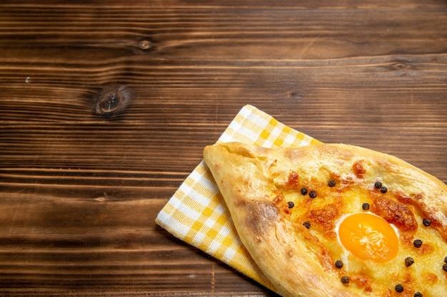 Vista frontal saboroso pão com ovo acabado de sair do forno na massa da secretária assar pão doce