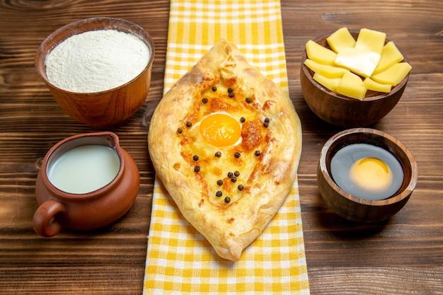 Vista frontal saboroso pão com ovo recém saído do forno com leite e queijo na mesa de madeira