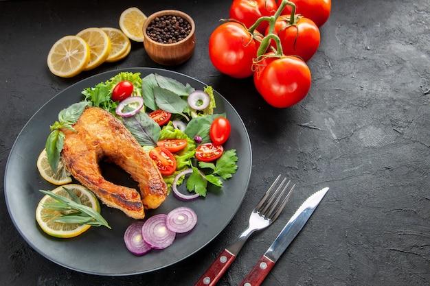 Vista frontal saboroso peixe cozido com legumes frescos e talheres em fundo escuro cor de comida foto prato carne frutos do mar crus