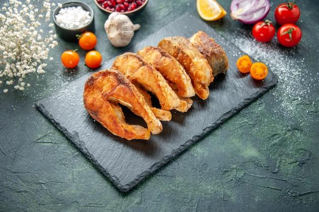 Vista frontal saboroso peixe frito com tomate na superfície azul escuro prato pimenta prato fritar frutos do mar carne do mar