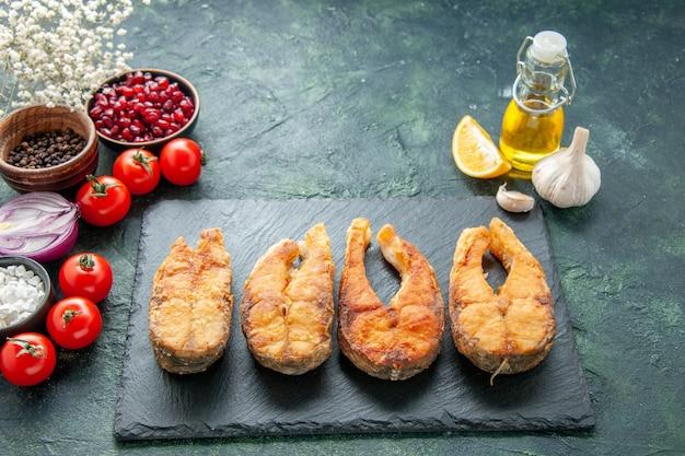 Vista frontal saboroso peixe frito com tomate na superfície escura cozinhando prato comida salada fritar refeição frutos do mar pimenta mar
