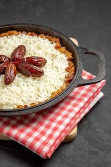 Vista frontal saboroso prato de arroz cozido com passas na superfície escura prato de passas prato de arroz com óleo