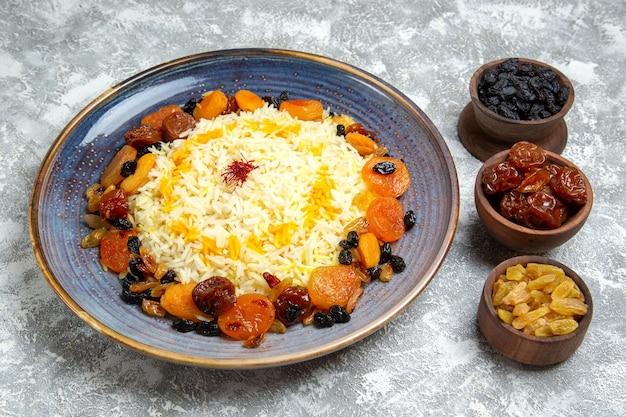 Vista frontal saboroso shakh plov prato de arroz cozido com passas dentro do prato no chão branco jantar cozinhando prato de arroz