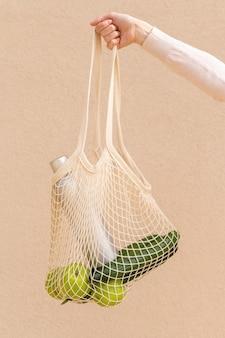 Vista frontal saco reutilizável com alimentos realizada pela mão da mulher