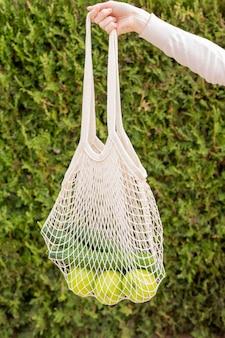 Vista frontal saco reutilizável com compras realizada pela mão da mulher na natureza