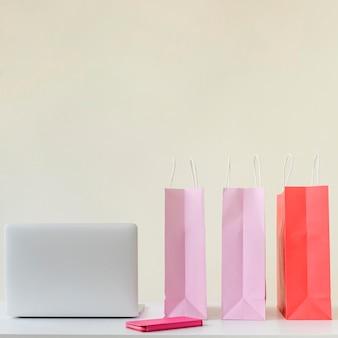 Vista frontal sacolas e laptop em cima da mesa
