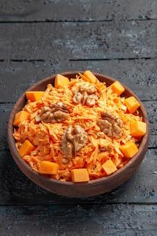 Vista frontal salada de cenoura fresca salada ralada com nozes e alho na mesa escura dieta salada madura cor saudável
