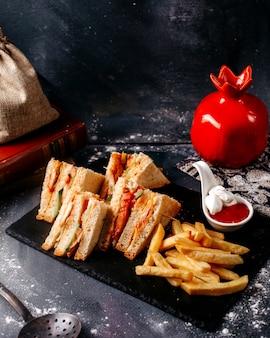 Vista frontal sanduíches, juntamente com batatas fritas na superfície cinza