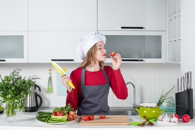 Vista frontal satisfeita cozinheira de avental cheirando tomate cortado