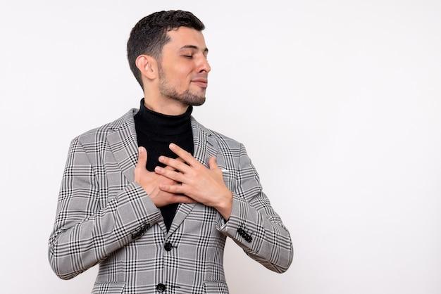 Vista frontal satisfeito bonito homem de terno fechando os olhos em pé sobre um fundo branco