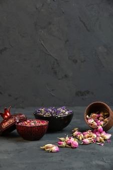 Vista frontal secas rosas espalhadas de um frasco com flores secas roxas em um vaso