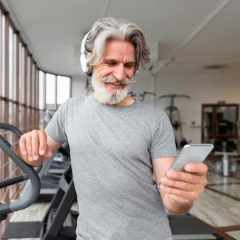 Vista frontal, segurando o smartphone no ginásio