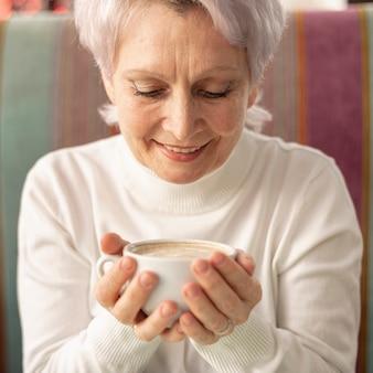 Vista frontal sênior feminino segurando a xícara de café