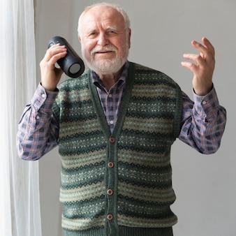 Vista frontal sênior tocando músicas no alto-falante