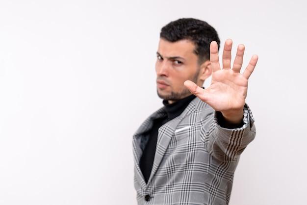 Vista frontal sério homem bonito em terno fazendo sinal de pare em pé sobre fundo branco isolado