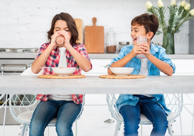 Vista frontal smiley irmãos comendo juntos