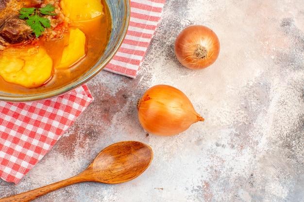 Vista frontal sopa bozbash toalha de cozinha uma colher de pau cebolas em fundo nu cozinha azerbaijana