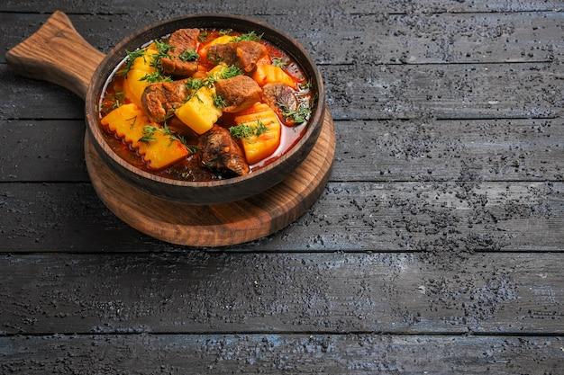 Vista frontal sopa de molho de carne com batatas e verduras na mesa escura.