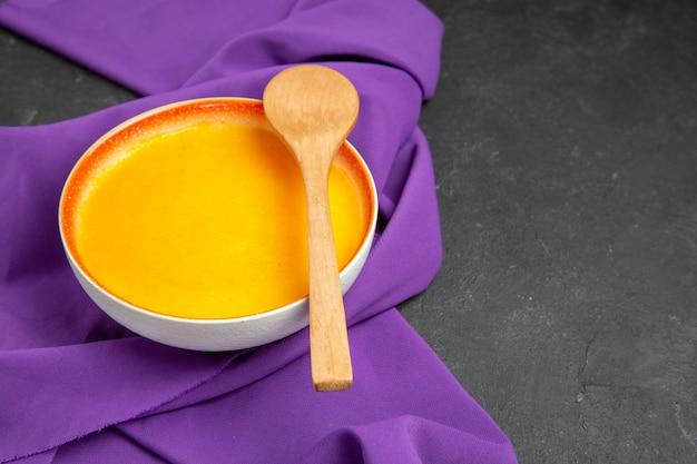 Vista frontal sopa simples de abóbora em tecido roxo e mesa escura de ação de graças jante suave